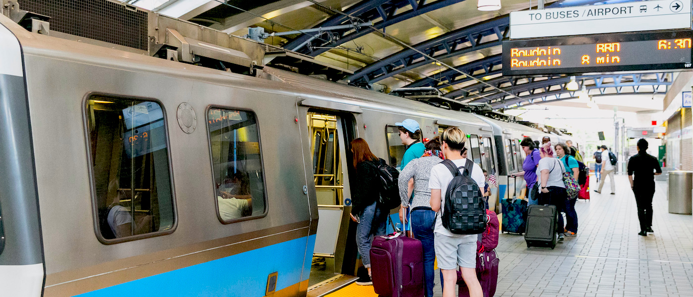 Passengers board a Blue Line Train at Airport Station