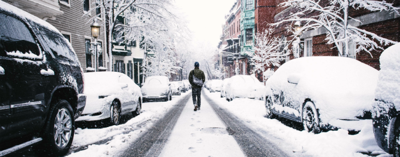 Man walking on a snowy road. Photo by Alice Donovan Rouse on Unsplash.