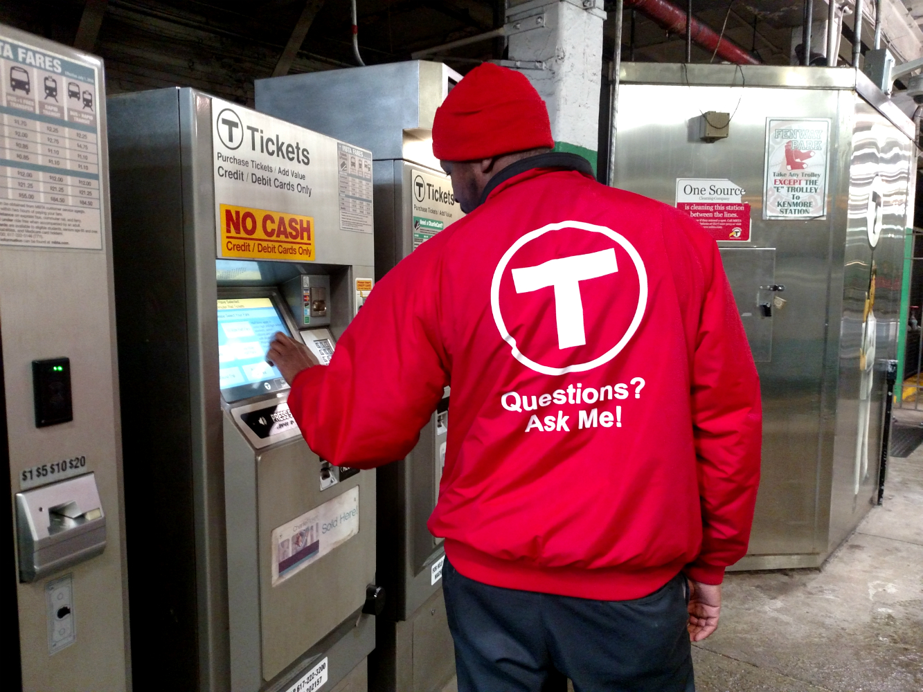 Transit Ambassador in a red jacket with 'Questions? Ask Me!' printed in white on the back. His back is to the camera, and he is tapping a fare vending machine screen.