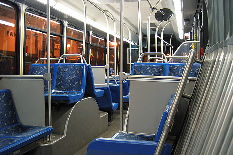 Interior of a Silver Line bus, with bright lighting and blue carpeted seats