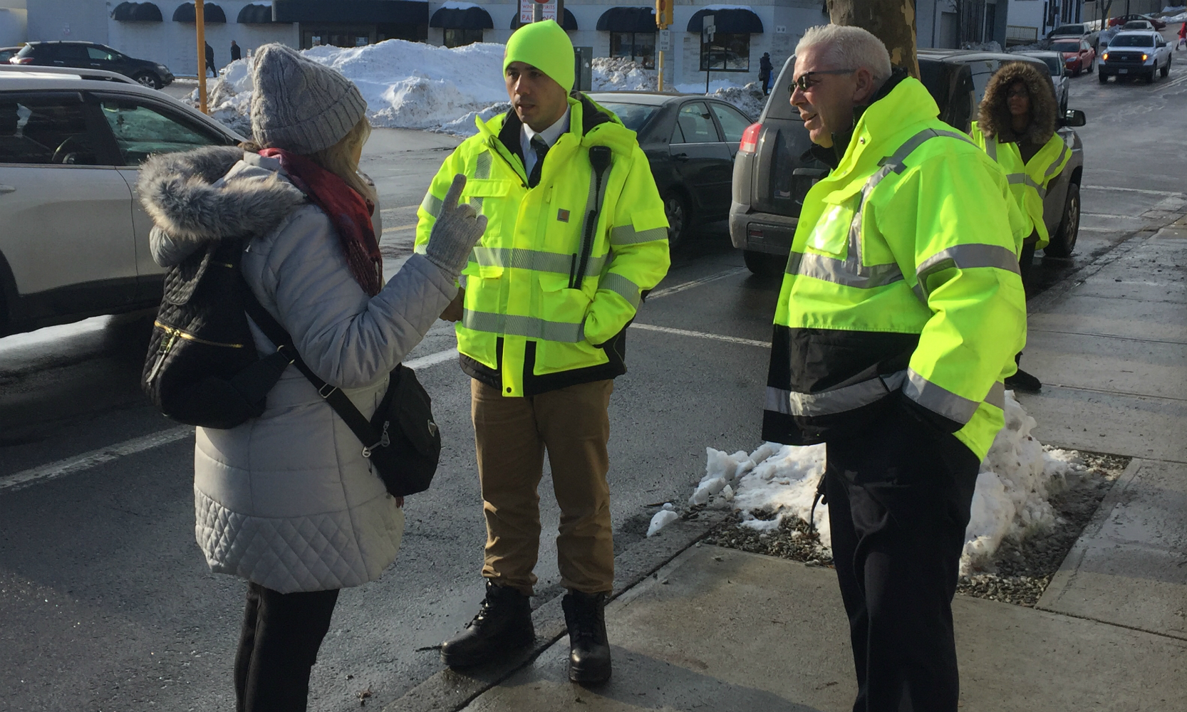 Two crewmen in neon jackets answer the question of a woman.