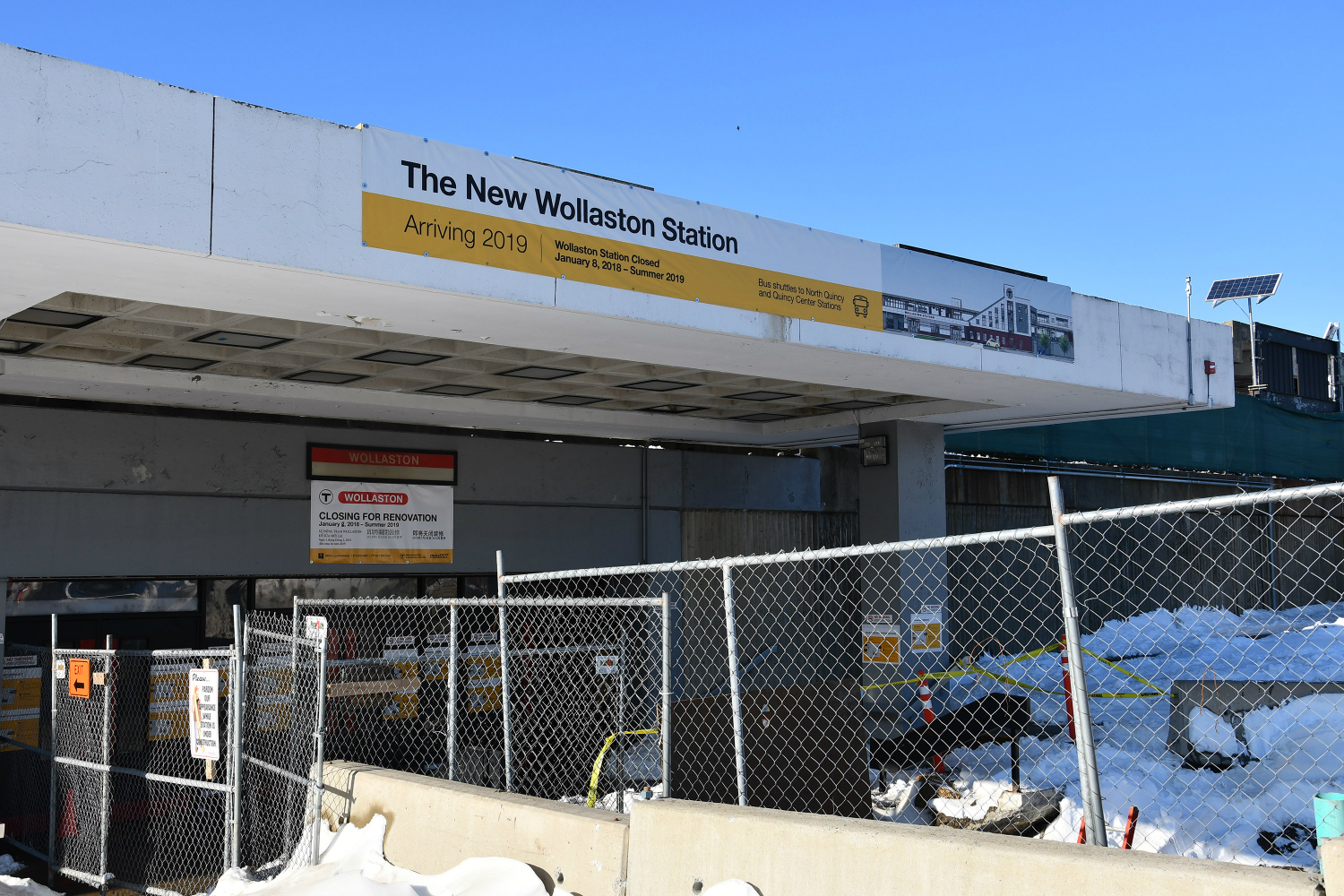 Wollaston Station with a banner that says, 'The New Wollaston Station Arriving 2019.' Fencing blocks off the station to passengers. There is also a smaller sign that says 'Closed for Renovation.'