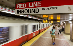 Red Line platform with a train leaving and passengers walking.