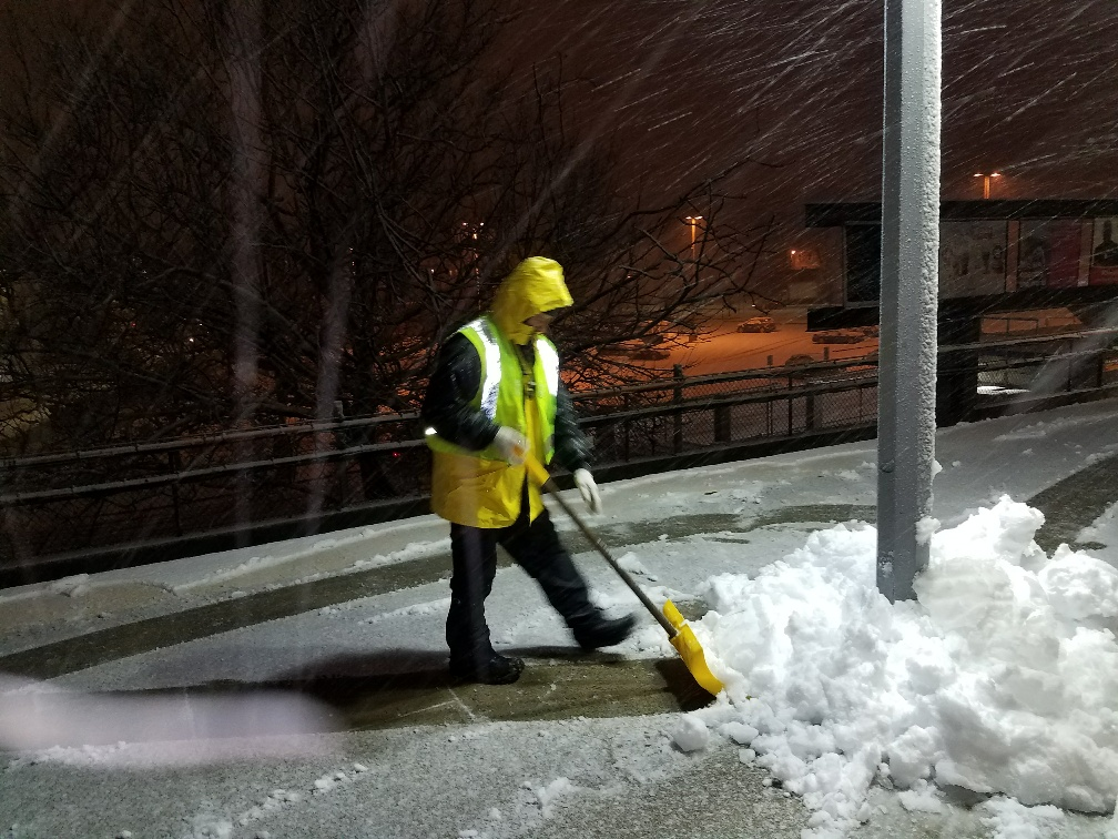 A crewperson clears snow from the platform at Malden Station.