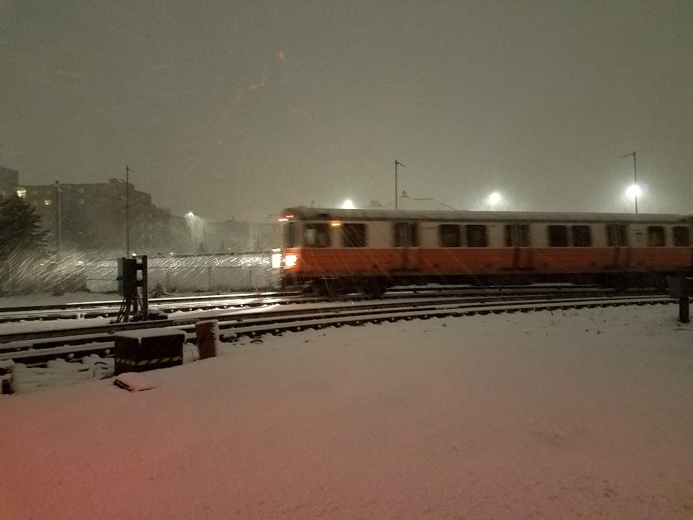At Wellington Yard, an Orange Line trains runs in the early morning snow, its headlights cutting through the darkness.