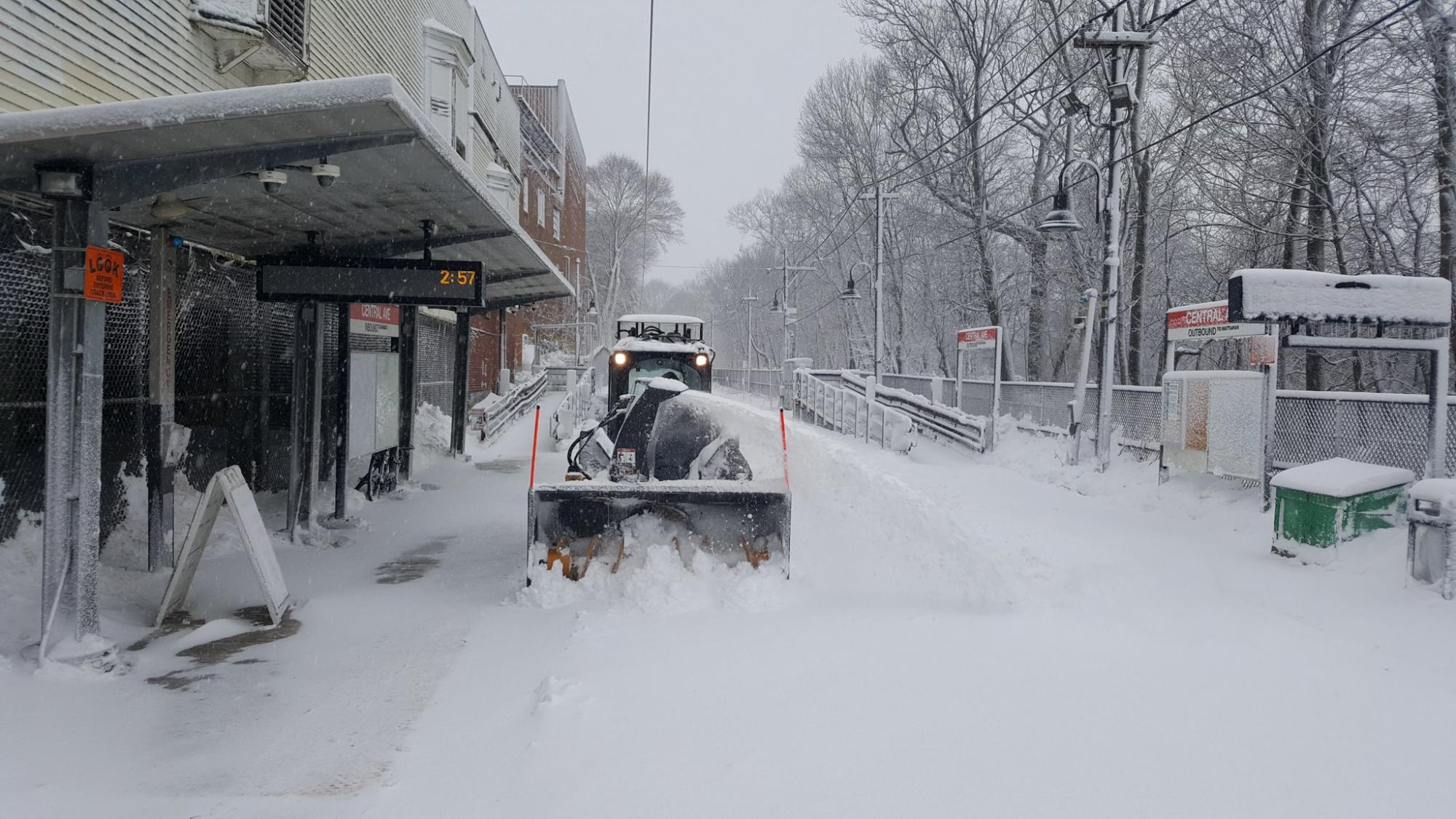 A large snow plow goes down the Mattapan Trolley's tracks at Central Ave station, clearing snow.