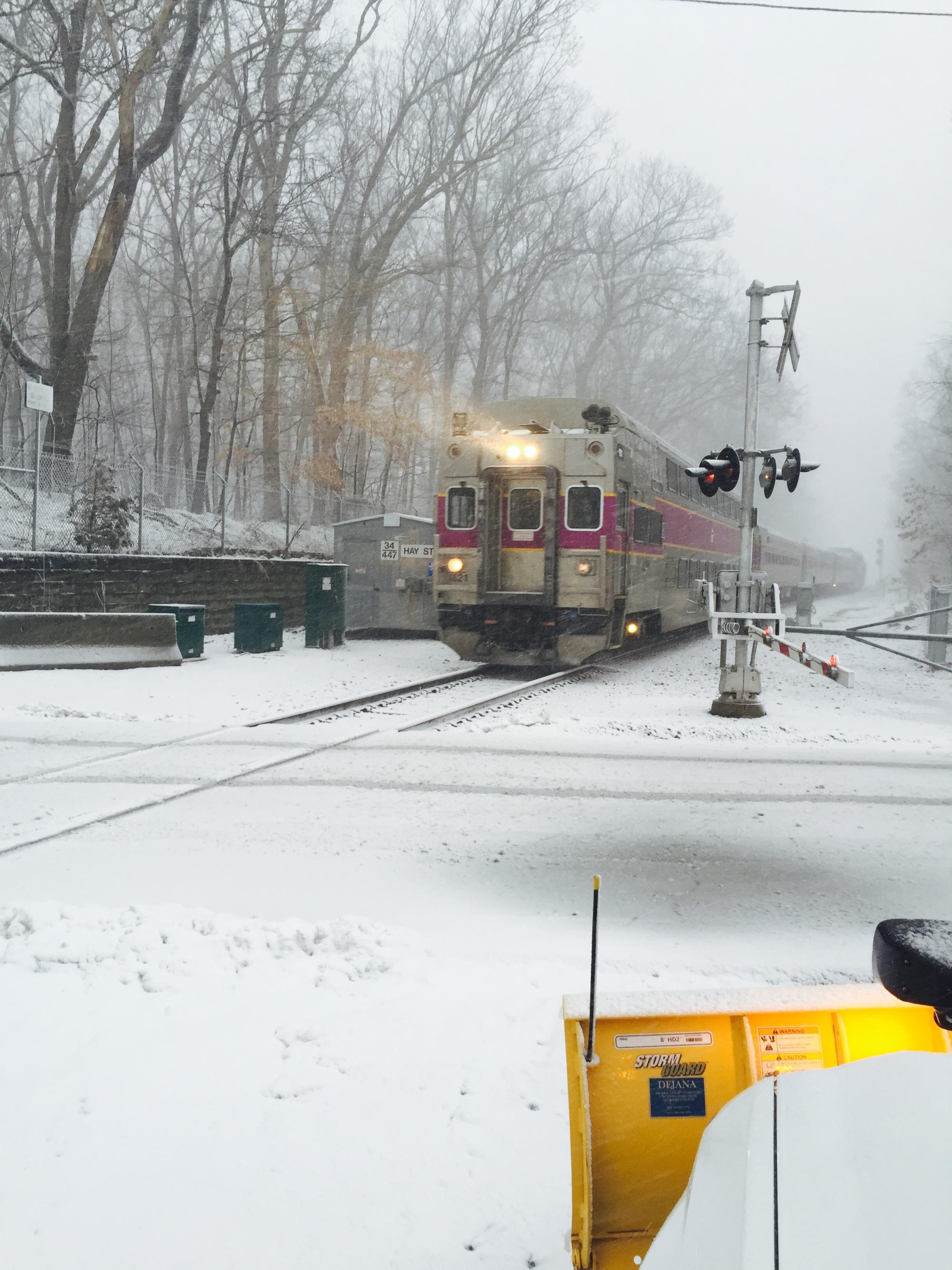 A Commuter Rail train pulls up to a crossing. In the immediate foreground, the front of a snow plow. Trees on the left.
