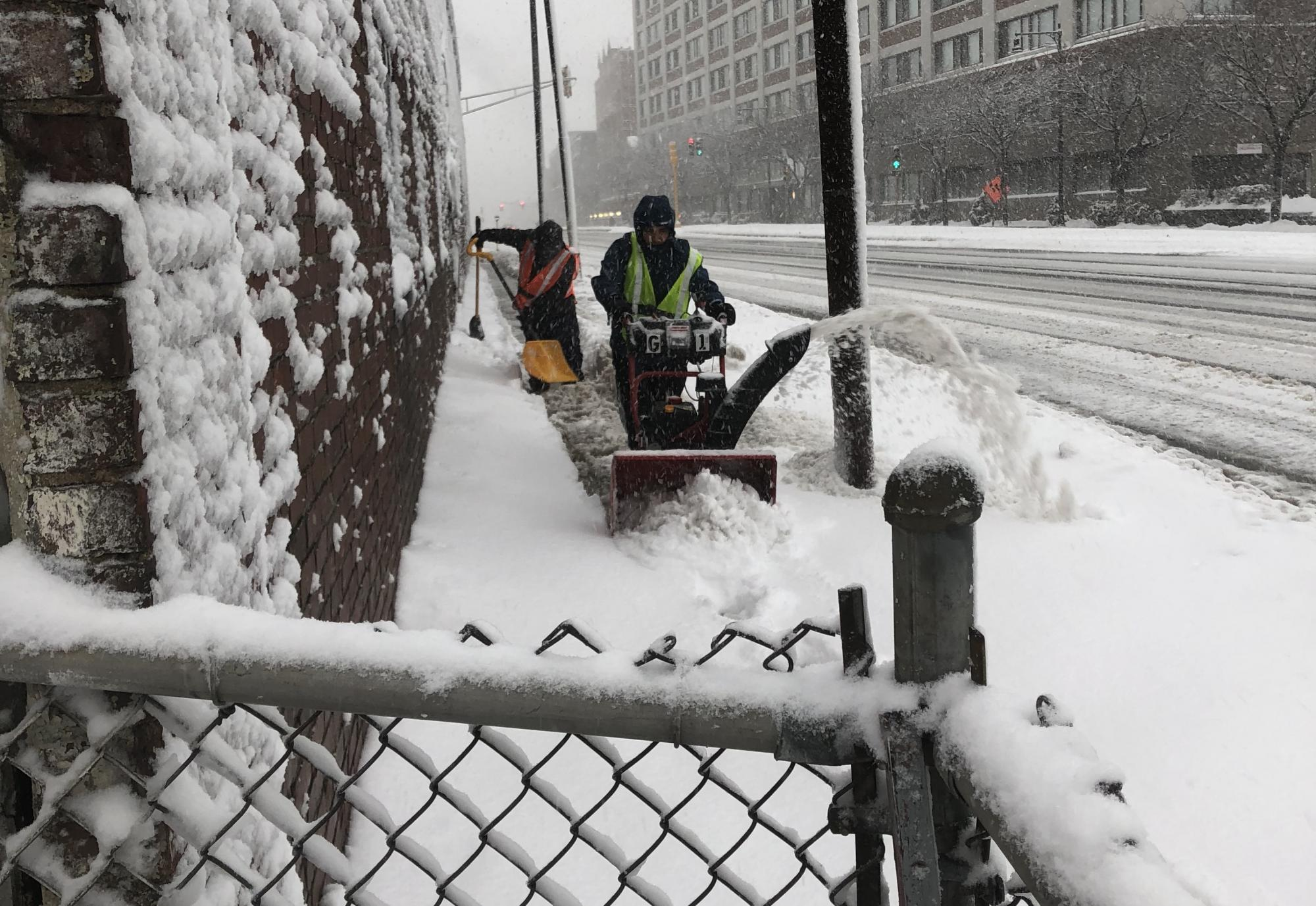 Two crew people on the sidewalk. The one in the back uses a shovel, while the one in the front uses a snow blower.