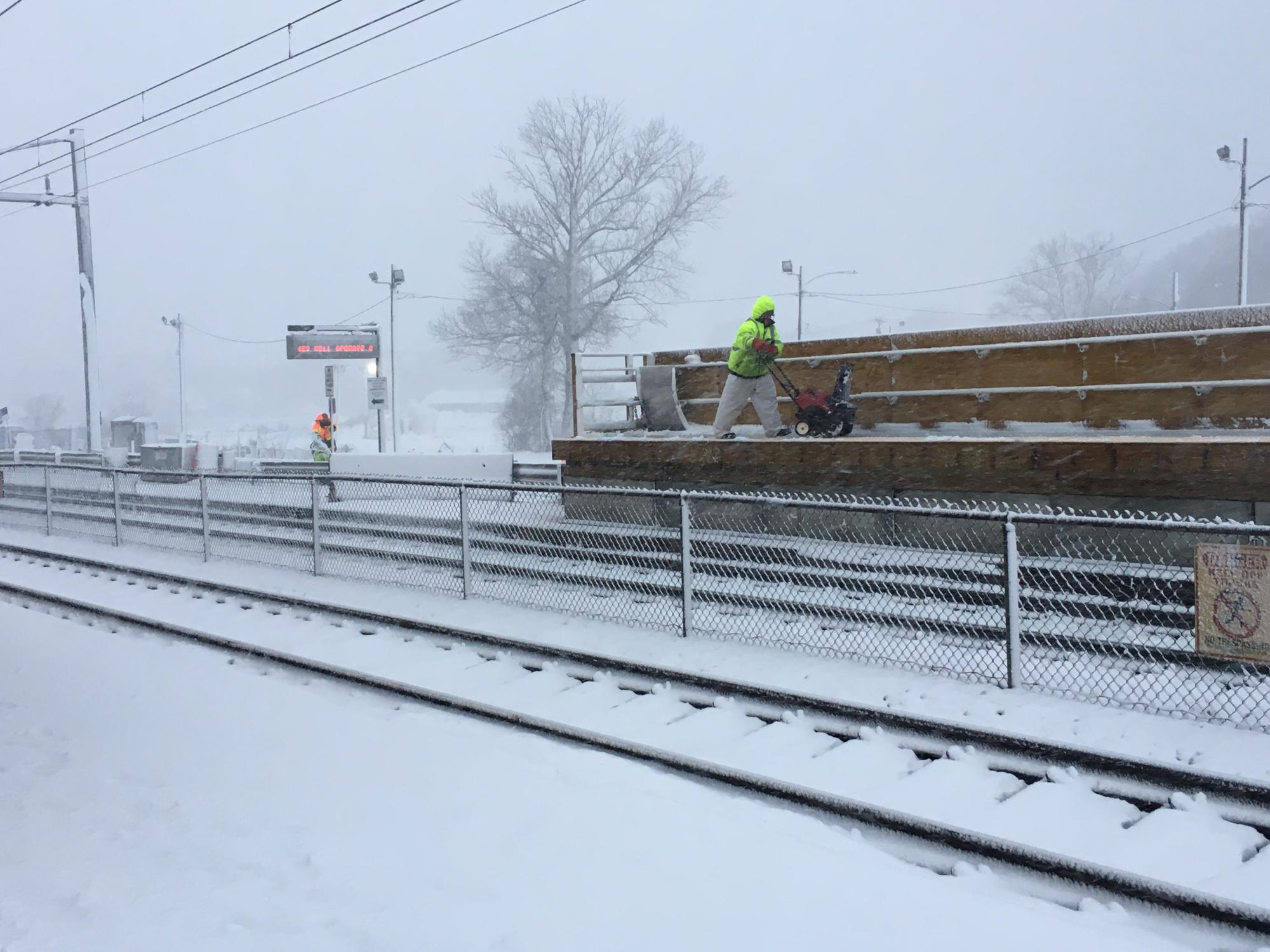Two crewpeople clear the platforms at Mansfield Commuter Rail station on the Providence/Stoughton Line. One is wearing a neon yellow vest and is using a snowblower on a temporary mini-high accessibility platform. The other is wearing an orange vest and is underneath the countdown sign.
