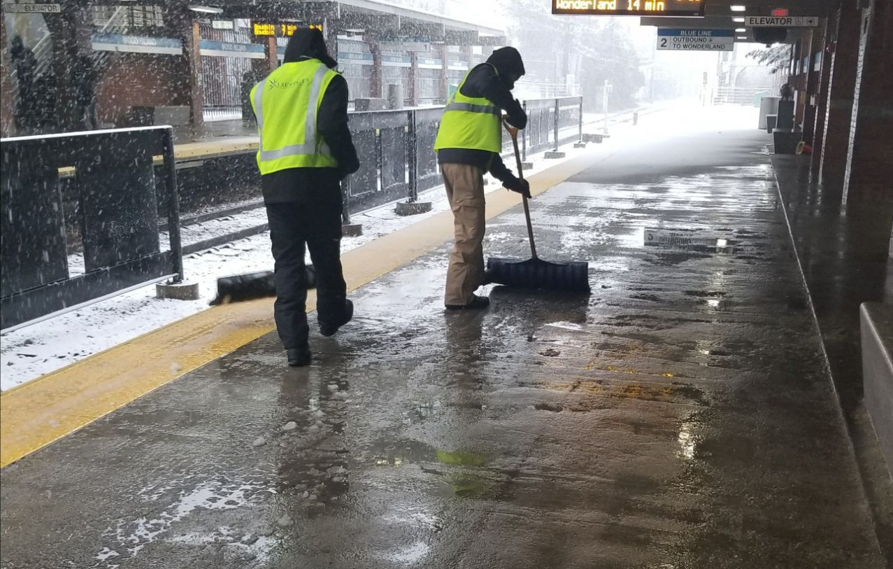 Two crewpeople in neon vests clear the platform at Wood Island station.